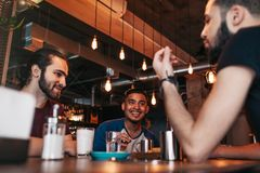 Homens novos árabes felizes que penduram no café do sótão Melhores amigos que falam na barra da sala de estar Passando o tempo li Foto de Stock Royalty Free