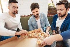 Homens novos atrativos que tomam fatias de pizza Fotografia de Stock