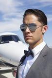 Homens novos consideráveis que vestem óculos de sol com plano privado no fundo imagens de stock royalty free