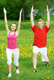 Homem novo e mulher que fazem esticando exercícios Imagens de Stock Royalty Free