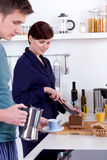 Homem novo e mulher feliz que preparam o pequeno almoço em sua cozinha fotografia de stock royalty free