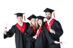 Homens novos e mulheres nos tampões acadêmicos que guardam certificados e sorriso Imagens de Stock Royalty Free