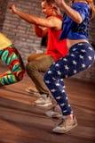 Homens novos e mulheres que dançam a coreografia moderna do grupo de Zumba imagens de stock