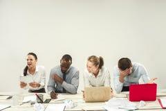 Homens novos e mulheres que sentam-se no escritório e que trabalham em portáteis Conceito das emoções imagem de stock