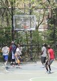 Homens novos na ação que joga a bola da cesta na rua Fotos de Stock Royalty Free
