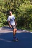 Homens novos na estrada com longboard fotos de stock
