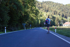 Homens novos na estrada com longboard Foto de Stock Royalty Free