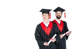 Homens novos nos tampões acadêmicos que guardam diplomas e que sorriem no branco Fotos de Stock