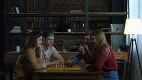 Homens novos que ensinam o jogo de xadrez às amigas alegres vídeos de arquivo