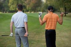 Homens novos que estão no campo de golfe com varas, vista traseira Fotografia de Stock