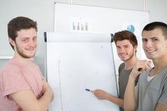 Homens novos que fazem a apresentação do negócio para agrupar fotos de stock