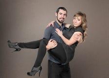 Homens novos que guardam a mulher nos braços Foto de Stock Royalty Free