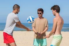 Homens novos que jogam a bola da salva na praia Fotografia de Stock
