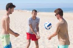 Homens novos que jogam a bola da salva na praia Fotos de Stock Royalty Free