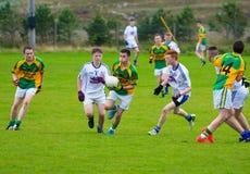 Homens novos que jogam um fósforo do futebol gaélico Fotografia de Stock Royalty Free