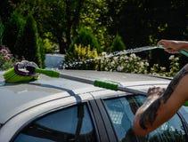 Homens novos que lavam o carro de prata com água exercida pressão sobre e a escova no dia ensolarado Feche acima do carro da limp Imagens de Stock