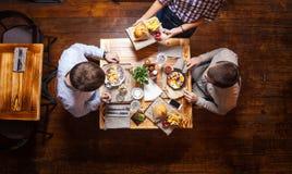 Homens novos que têm o almoço em um café Fotografia de Stock Royalty Free