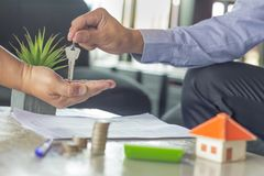 Homens novos que tomam chaves do mediador imobiliário masculino durante a reunião imagens de stock