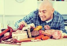 Homens ordinários com lotes de produtos da carne e de salsicha Imagem de Stock Royalty Free