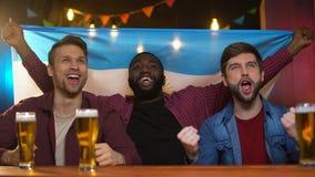 Homens pretos e caucasianos emocionais que cheering para a equipe de futebol argentina, barra vídeos de arquivo