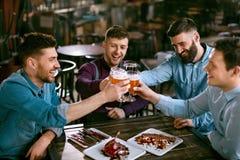 Homens que bebem a cerveja no bar imagem de stock