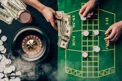 Homens que colocam uma aposta na tabela do casino imagem de stock