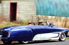 Homens que conduzem 1952 o convertible da porta do costume dois de Dodge dos anos 50 na movimentação do país Foto de Stock
