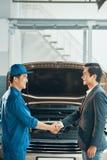 Homens que cooperam no auto serviço fotografia de stock royalty free