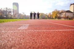 Homens que correm em pistas da trilha do atletismo Imagem de Stock