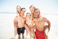 Homens que dão um reboque às mulheres na praia Imagem de Stock Royalty Free
