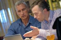 Homens que discutem a informação na tela da tabuleta fotos de stock