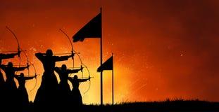 Homens que disparam em setas com curva no campo de batalha fotografia de stock