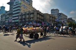 Homens que empurram o vagão dos sacos em Dhaka Fotos de Stock Royalty Free