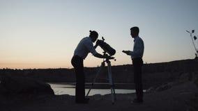 Homens que exploram o espaço com telescópio Imagens de Stock Royalty Free