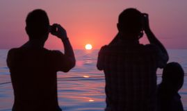Homens que fotografam o nascer do sol no mar Foto de Stock Royalty Free