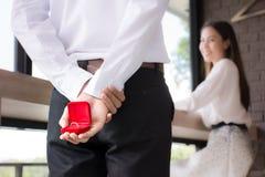 Homens que guardam uma caixa da aliança de casamento atrás para surpreender uma amiga fotografia de stock royalty free
