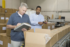 Homens que inspecionam bens no armazém fotos de stock royalty free