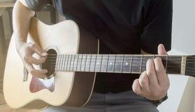 Homens que jogam o Em do cabo do close up da guitarra acústica com luz solar Fotografia de Stock Royalty Free