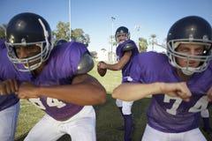 Homens que jogam o futebol americano no campo Imagens de Stock Royalty Free