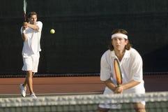 Homens que jogam o tênis no campo de ténis Fotografia de Stock Royalty Free