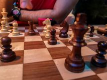 Homens que jogam a xadrez - rei e partes de xadrez em uma placa de madeira imagem de stock royalty free