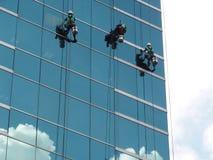 homens que limpam a construção de vidro pelo acesso da corda na altura Foto de Stock