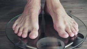 Homens que medem o peso na escala da saúde vídeo de 3840X2160 UHD filme