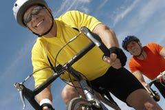 Homens que montam bicicletas contra o céu Imagens de Stock Royalty Free