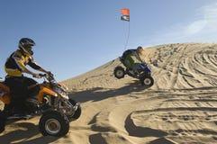 Homens que montam bicicletas do quadrilátero no deserto foto de stock