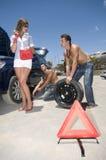 Homens que mudam uma roda para ajudar uma mulher Imagem de Stock Royalty Free