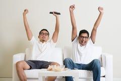 Homens que olham o fósforo de futebol na tevê junto Imagem de Stock
