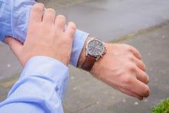 Homens que olham o relógio de pulso Imagem de Stock Royalty Free