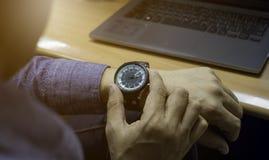 Homens que olham os relógios que são vestidos nas mãos, para verificar o tempo fotos de stock