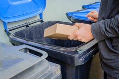 Homens que põem a caixa de papel do cartão no recipiente azul do lixo foto de stock royalty free
